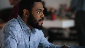 Homem africano considerável novo feliz do close-up na roupa formal que sorri, falando na tabela moderna na moda do escritório do  vídeos de arquivo
