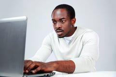 Homem africano de Concetrated que usa o portátil Fotografia de Stock Royalty Free