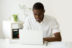 Homem africano de sorriso que usa o portátil que senta em casa a mesa de escritório imagens de stock royalty free