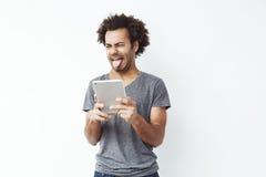 Homem africano desagradado que mostra a língua que guarda a tabuleta sobre o fundo branco Fotografia de Stock