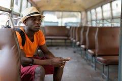 Homem africano do turista que pensa ao guardar o telefone celular fotografia de stock