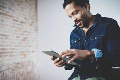Homem africano farpado atrativo que usa a tabuleta em seu escritório domiciliário moderno Conceito dos jovens que trabalham dispo imagens de stock
