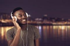 Homem africano feliz que anda na praia quando música de escuta com fones de ouvido Fotos de Stock