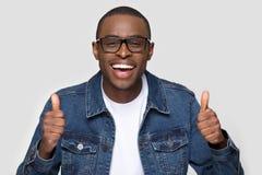Homem africano feliz que mostra os polegares acima da c?mera de vista de riso fotos de stock