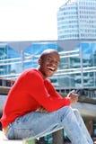 Homem africano feliz que senta-se fora de usar o telefone e do rir fotografia de stock