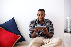 Homem africano feliz que usa a tabuleta digital em casa fotos de stock royalty free