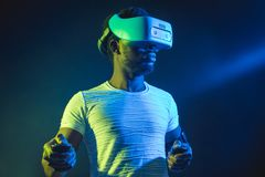 Homem africano no branco, auriculares vestindo de VR no fundo duplo azul verde da cor fotografia de stock