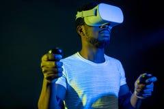 Homem africano no branco, auriculares vestindo de VR no fundo duplo azul verde da cor foto de stock