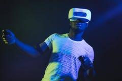 Homem africano no branco, auriculares vestindo de VR no fundo duplo azul verde da cor fotografia de stock royalty free