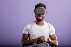 Homem africano novo consider?vel na posi??o dos auriculares de VR contra o fundo roxo imagem de stock royalty free