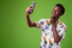 Homem africano novo do turista pronto para férias contra o backg verde foto de stock