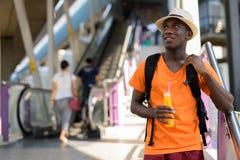 Homem africano novo do turista que guarda o suco de laranja perto da escada rolante fotografia de stock royalty free