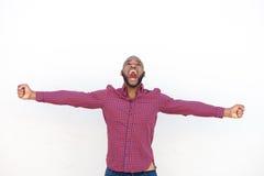 Homem africano novo entusiasmado com a gritaria estendido dos braços fotografia de stock royalty free