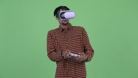 Homem africano novo feliz que joga jogos com os auriculares da realidade virtual filme