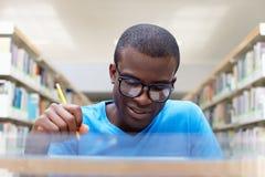 Homem africano novo que estuda na biblioteca fotos de stock royalty free