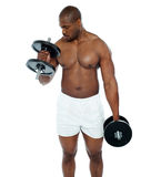 Homem africano novo que faz o exercício do bíceps imagem de stock