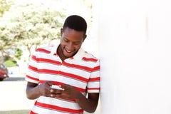 Homem africano novo que usa o telefone celular fora fotos de stock