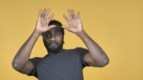Homem africano ocasional confundido e assustado dos problemas isolados no fundo amarelo filme