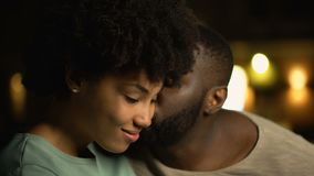 Homem africano que beija a amiga tímida no mordente, par que abraça a data romântica da noite video estoque