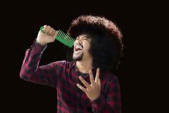 Homem africano que canta com um pente do cabelo Foto de Stock Royalty Free