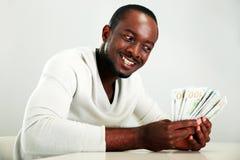 Homem africano que guarda dólares americanos Fotografia de Stock