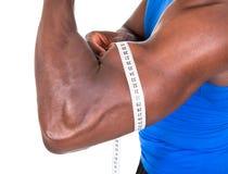 Homem africano que mede seu bíceps foto de stock royalty free