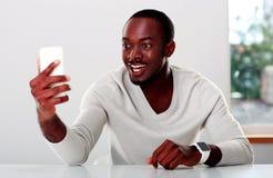 Homem africano que olha no smartphone imagem de stock