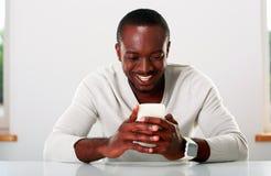 Homem africano que usa o smartphone imagens de stock royalty free