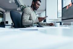 Homem africano que usa o telefone esperto foto de stock royalty free