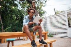 Homem africano sério que escuta a música e que usa a tabuleta fora fotografia de stock