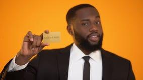 Homem afro-americano à moda no terno que mostra o cartão do ouro, sociedade do clube da elite filme