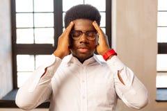 Homem afro-americano agradável que tenta concentrar-se fotografia de stock