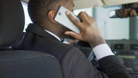 Homem afro-americano ansioso que chama alguém do carro, muitos tempos de espera video estoque