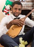 Homem afro-americano com instrumento musical Dombra pela chaminé Natal Fotografia de Stock