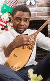 Homem afro-americano com instrumento musical Dombra pela chaminé Natal Fotos de Stock Royalty Free