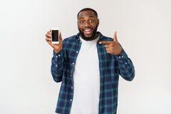 Homem afro-americano considerável isolado no fundo cinzento, apresentando o telefone esperto imagem de stock royalty free