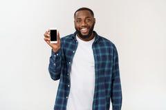 Homem afro-americano considerável isolado no fundo cinzento, apresentando o telefone esperto imagens de stock