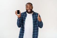 Homem afro-americano considerável isolado no fundo cinzento, apresentando o telefone esperto fotografia de stock