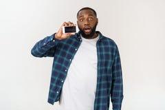 Homem afro-americano considerável isolado no fundo cinzento, apresentando o telefone esperto imagens de stock royalty free