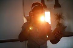 Homem afro-americano considerável que escuta a música na tabuleta imagens de stock