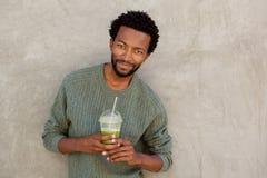 Homem afro-americano considerável que guarda a bebida do suco de fruto fotografia de stock royalty free
