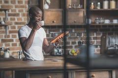 Homem afro-americano considerável que usa a tabuleta ao comer seu café da manhã foto de stock royalty free