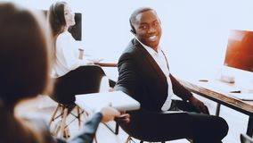 Homem afro-americano de assento que trabalha no centro de atendimento Gerente com computador homem no local de trabalho Consultan imagem de stock