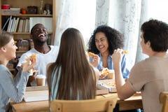 Homem afro-americano de riso feliz, apreciando a pizza com amigos imagens de stock