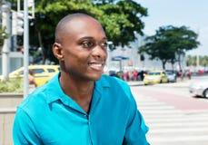 Homem afro-americano de riso na camisa brilhante que olha lateralmente imagens de stock