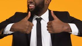 Homem afro-americano de sorriso no terno que mostra os polegares acima, promoção da carreira video estoque