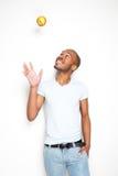 Homem afro-americano de sorriso que joga uma maçã no ar imagem de stock royalty free
