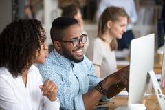 Homem afro-americano de sorriso que mostra a notícia engraçada ao colega foto de stock