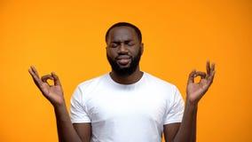 Homem afro-americano descontentado que medita para acalmar-se para baixo, aliviando o esfor?o imagens de stock royalty free