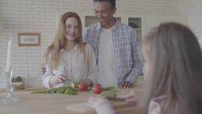 Homem afro-americano do retrato e mulher consideravelmente de sorriso que cozinham a posição da salada na tabela na cozinha moder video estoque